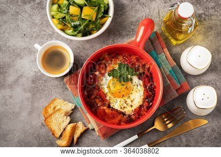 Shakshuka In A Red Pan, Coffee, Bread  And Salad In A Bowl, Gray Background, Copy Space