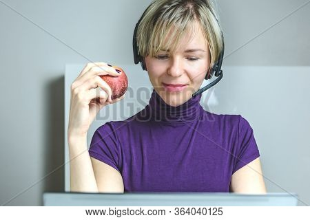 Caucasian Woman Working From Home With A Headset And Holding An Apple. Concept Of Healthy