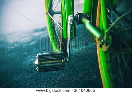 A Bright Green Old Retro Bike Stands On The Dark Asphalt In Spring Weather.
