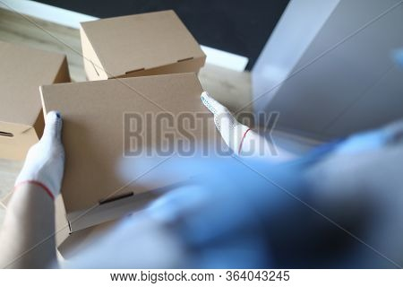 Close-up Of Deliveryman Holding Cardboard Box In Hands. Loader Transporting Things To New Apartment.