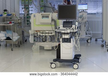 Ultrasound Machine, On Background Patient Connected To Medical Ventilator And Dialysis Machine . Pla