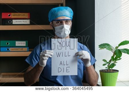 Sad Doctor In Blue Protective Uniform In A Mask And Glasses Shows The Inscription On A Paper Sheet W