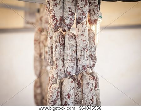 French Saucission Drying And Hanging In A Kitchen. Saucisson, Or Saucisse Seche, Is A Traditional Dr
