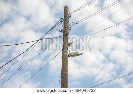 Electric Wooden Pole With Lamp And Electricity Cables Hanging On. Cloudy Sky.