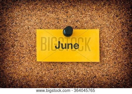 June Written On A Yellow Piece Of Paper That Is On A Bulletin Board. Close Up.
