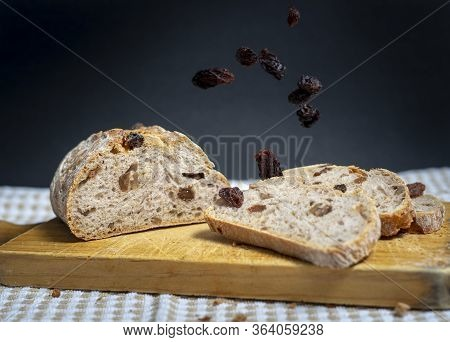 Raisins Falling From Above Onto Slices Of Homemade Bread With Raisins, Walnuts, Spices And Chopped N