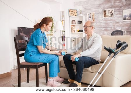 Female Doctor In Nursing Home Helping Old Man With His Rehabilitation Treatment.