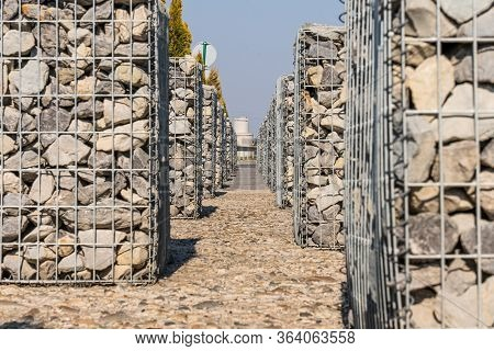 Detail Of A Low Gabion Wall. The Texture Of The Gabion Fence Is Made Of Natural Stone