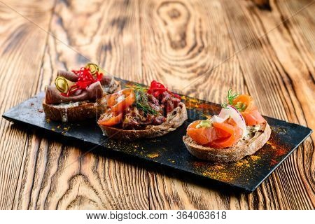 Set Of Many Different Bruschettas At Wooden Table Top. Italian Cuisine Appetizer With Many Ingridien