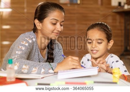 Young Girl Teaching Her Sister At Home - Conept Of Homeschooling During Coronavirus Or Covid-19 Lock