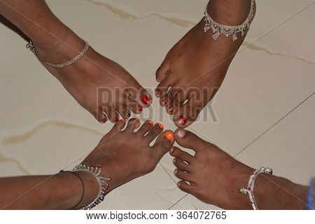 Close Up Of Four Legs Of Girls Wearing Silver Ankle Bracelets, Payals, Selective Focusing