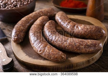 Freshly Made Rustic Sausages On A Wood Cutting Board.