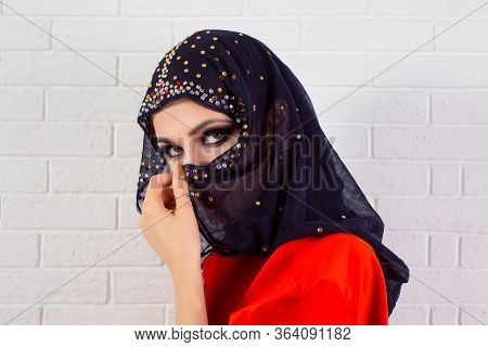 Beautiful Shy Muslim Woman Covering Face With Fashion Veil - On White Bricks Wall Background. Closeu