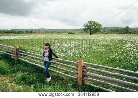 A Tourist Young Woman Standing Near To The Fence At Flowering Wild Narrow Leaf Narcissus Field In Na