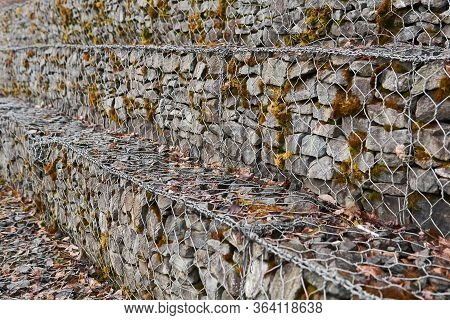 Stepped Gabion Wall Of Hexagonal Wire Netting With Granite Boulders Blurred In Perspective
