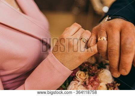 Newlyweds Holding Each Other With Little Fingers And Showing Their Wedding Rings. Wedding Day.