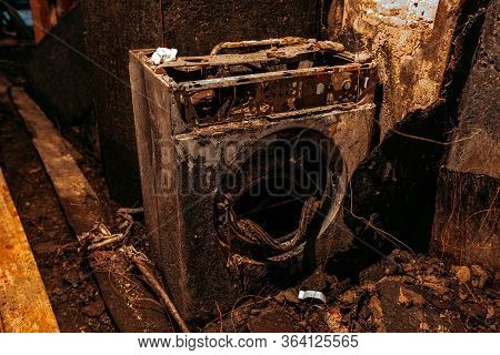 Burnt House Interior. Burned Burnt Bathroom, Fused Remains Of Furniture And Washing Machine