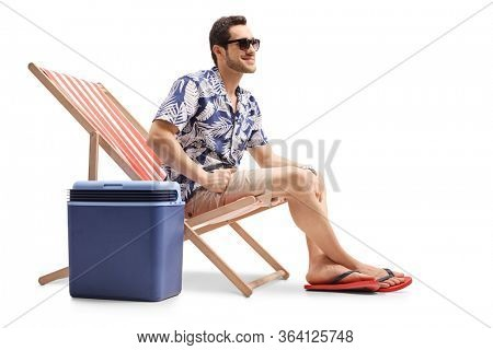 Young male tourist sitting on a deck chair with a cooling box isolated on white background