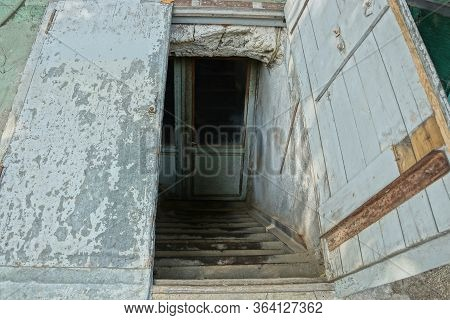 Descent To The Basement On The Street With Stone Steps And An Open Shabby Old Wooden Door