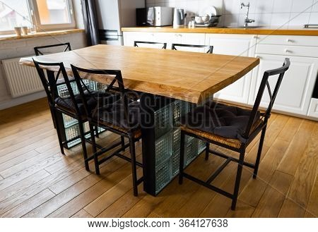 A Big Wooden Dining Table With Glass Blocks And Metal Wicker Chairs And Pillows In Modern Scandinavi