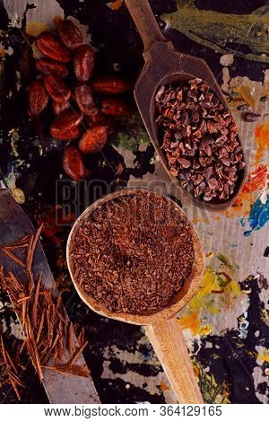raw cacao nibs, shredded chocolate and cocoa beans  on vintage dark metal background