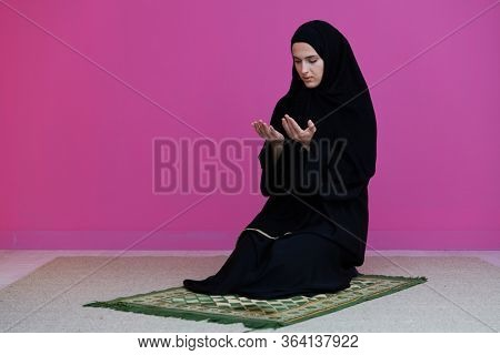 Muslim woman in namaz praying for Allah muslim god. Muslim woman on the carpet praying in traditional middle eastern clothes, Woman in Hijab