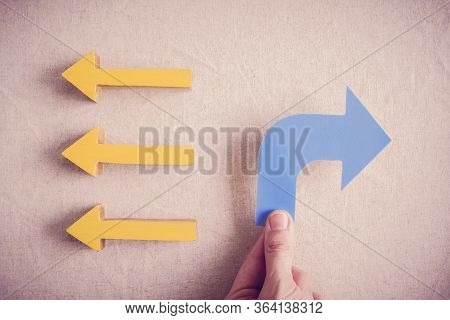 Hands Holding Blue Arrow To Opposite Direction Of Others, Disruptive Inovation And Change Business C