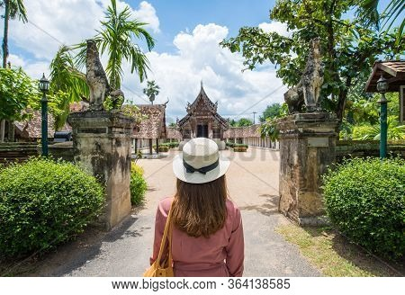 Back View Of Female Tourist Looking To The Beautiful Architecture Of Wat Inthrawat Temple Is One Of