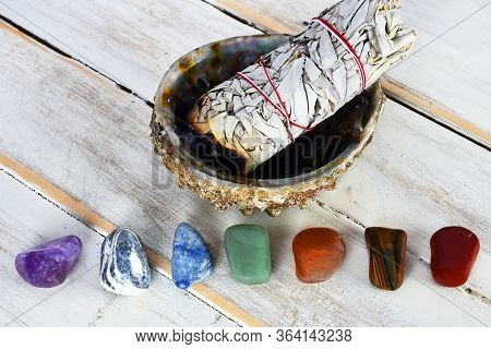 A Close Up Image Of Healing Chakra Crystals With A White Sage Bundle In An Abalone Shell.