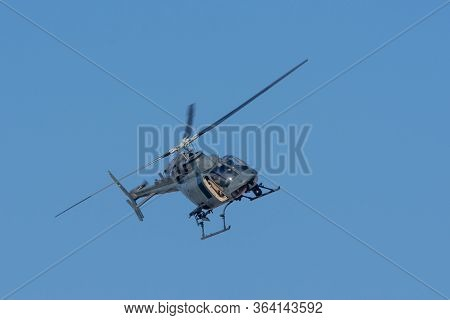 Military Chopper In War Flies On Angle Through The Sky. Military Concept Of Power, Force, Strength,