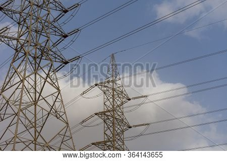 High Voltage Powerlines On Blue Sky And Cloudy Background In The Middle East.