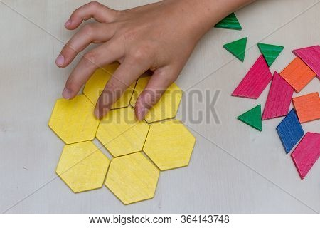 Tangram Hexagon Flower Colored Child Geometric Puzzle Piece With Hand Filling In Final Piece On Brow