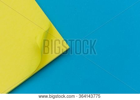 Bright Yellow Posted Note On Bright Blue Flat Lay Background For Education Or Business Organization