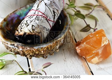 A Close Up Image Of A White Sage Bundle In An Abalone Shell With Honey Calcite On A White Wooden Tab