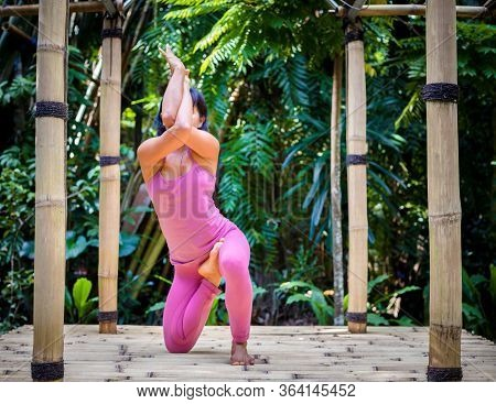 Yoga Practice Outdoor. Asian Yoga Teacher Practicing Variation Of Vrikshasana, Tree Pose. Garudasana