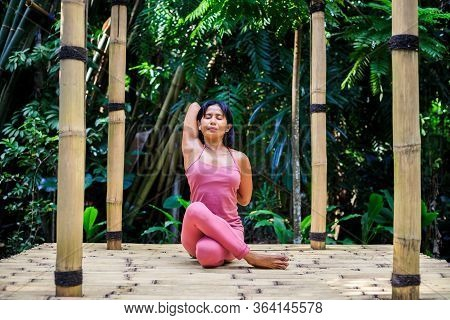 Yoga Practice Outdoor. Asian Yoga Teacher Practicing Gomukhasana, Cow Face Pose, Seated Asana In Hat
