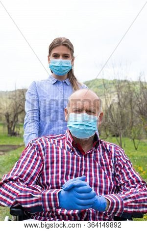Elderly Disabled Man With Mask Sitting In Wheelchair, Assisted By Young Female Caregiver Outdoors
