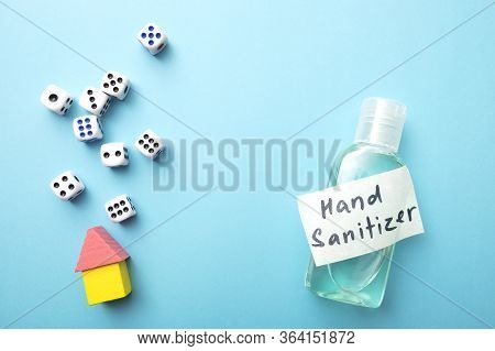 A Bottle Of Hand Sterilizer, A Little Yellow And Pink House And Dice On Blue Background. Hand Cleani