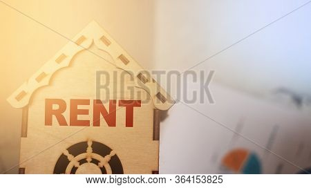 Miniature Toy Model House With Inscription Rent Letters Word On Wooden Backdrop. Real Estate Propert