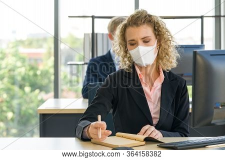 Young Blonde Staff In A Suit With A Face Mask Is Taking Notes Of What To Do After The Meeting. Reduc