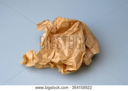 A Clump Of Crumpled Paper On A Gray Background. Crumpled Used Baking Paper Top View. A Clump Of Brow