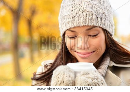 Fall woman drinking coffee in autumn city park. Girl enjoying hot drink from disposable coffee cup. Fall lifestyle concept with beautiful young mixed race Chinese Asian / Caucasian female model.