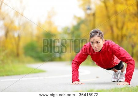 woman doing push-ups during outdoor cross training workout. Beautiful young and fit fitness sport model training outside in fall.