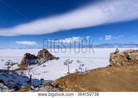Lake Baikal, Russia - March 11, 2020: Girl Looks To Cape Burhan On Shamanka Rock In Olkhon Island In