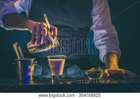 Bartender Preparing Cocktail In Shaker; Barman Pouring Baileys Comet Cocktail From Shaker Into Glass