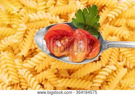 Cherry Tomato In Brine In A Silver Spoon On A Raw Pasta Background.
