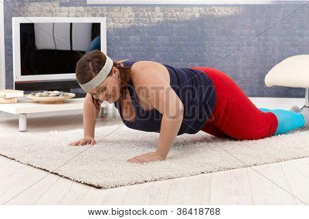 Übergewicht Frau doing Push-ups zu Hause, Lächeln.