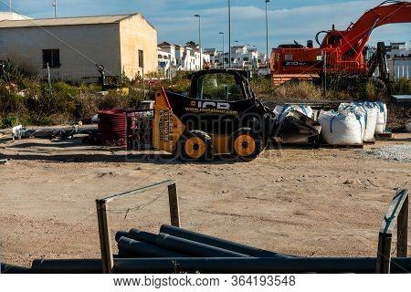 Torrevieja, Valenciana, Spain - May 02 2020 : Mini Jcb Digger In Builders Yard On Urbanisation In Sp