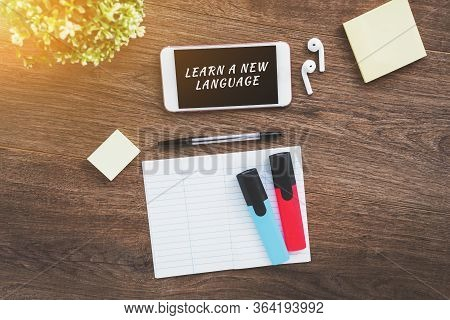 Learn A New Language - An Inscription On A Smartphone, A Notebook For Writing Foreign Words, Markers