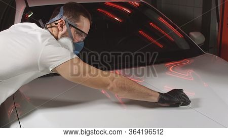 Polishing The Car With Ceramics, A Man Polishes The Car With Wax. Man In Glasses And A Mask, A Respi